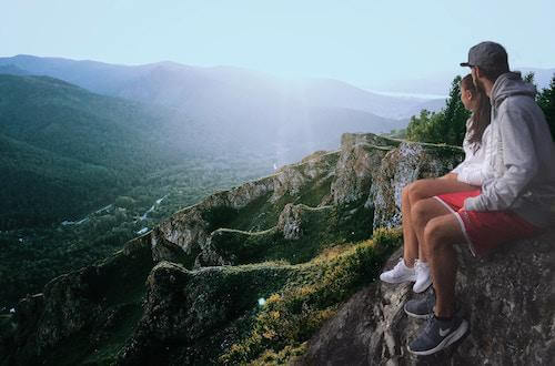 man, woman, sitting on a cliff watching the sunrise