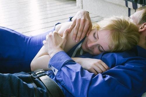 A couple in blue cuddling on the couch