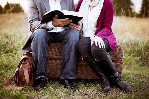 A couple reading together in a field