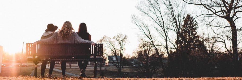three women sitting on bench facing backward watching sunset