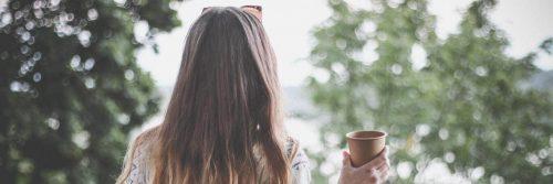 woman stands facing backward holding cup looking at trees lake