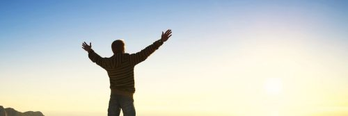 man stands alone raising hands feeling grateful about life in sunny blue sky