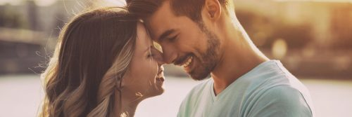 couple stands head to head happily smiling in sunny sky