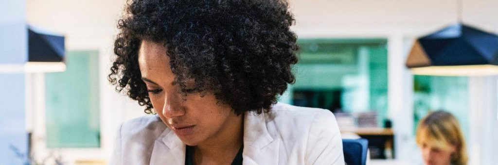 curly black hair woman wearing white vest sits in office focusing on work