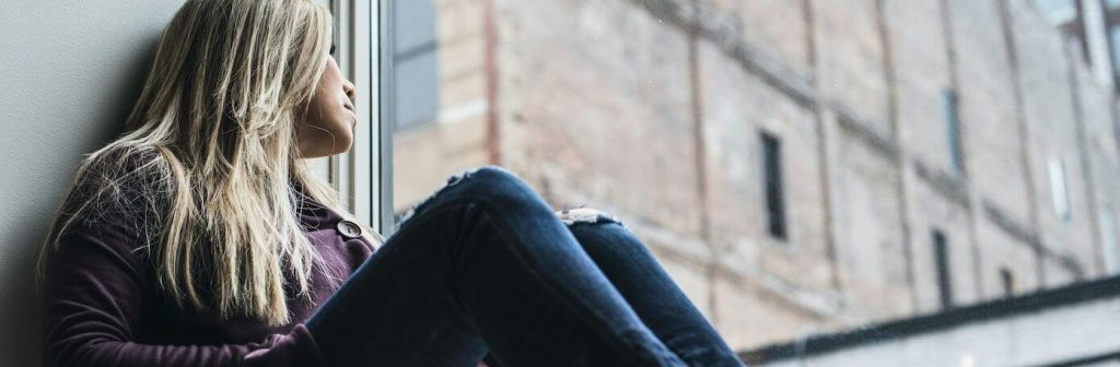 woman sits next to window looking at tall old building