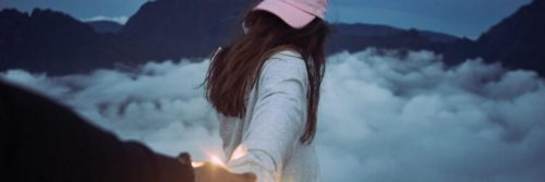 woman facing backward wearing pink cap holding partner hand walking in cloudy sky