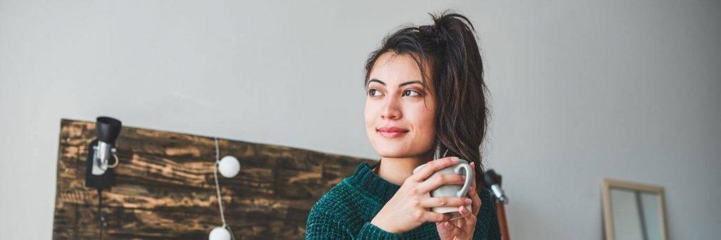 woman smiles holds white mug