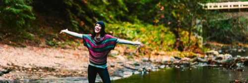 woman excitedly happily standing besides lake gratitude life in forest