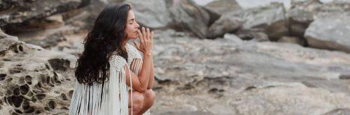 woman sits on rock eyes closed focusing on thinking breathing meditation in peaceful environment