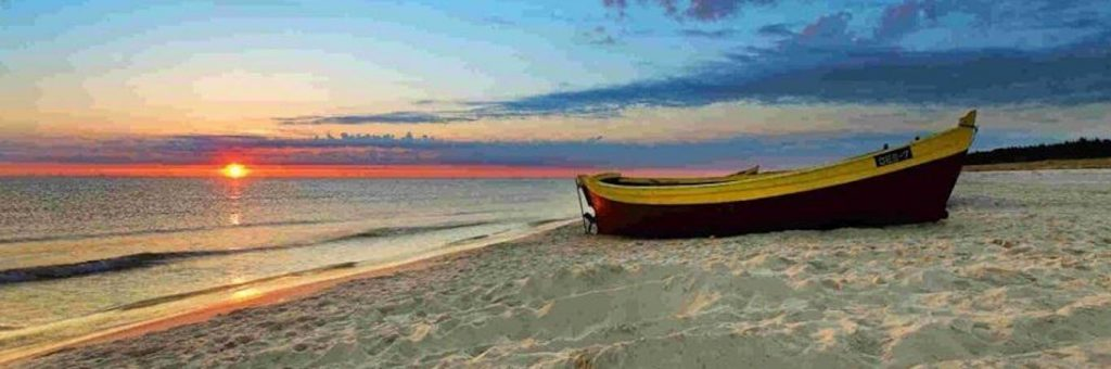 boat on sand nearby beach in blue sunset sky