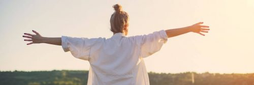 woman facing backward gratitude life in sunny sky