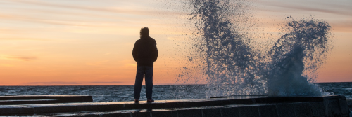 man stands on seaport looking at strong ocean wave in sunset sky