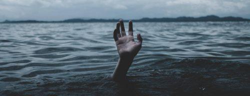hand raises over water ocean in overcast weather