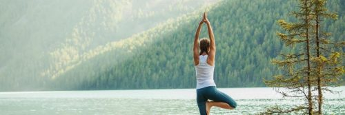 woman stands practicing yoga near lake in beautiful sunny sky