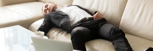 man tiredly sleeps on couch beside laptop coffee mug