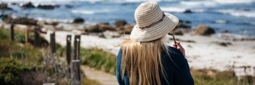 woman facing backward walking along coastal walk beside blue ocean rocks
