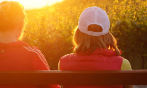 two women sits on bench facing backward watching sunset
