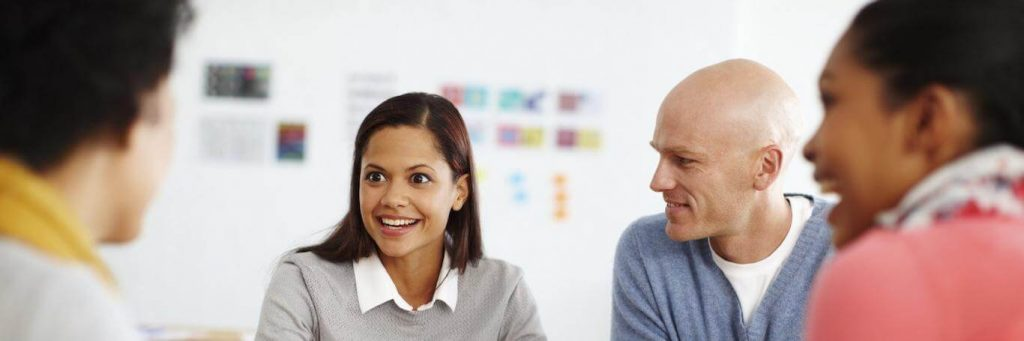 group of people happily communicates discusses in co working room