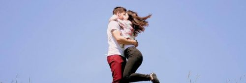 couple stands hugging each other in blue sky