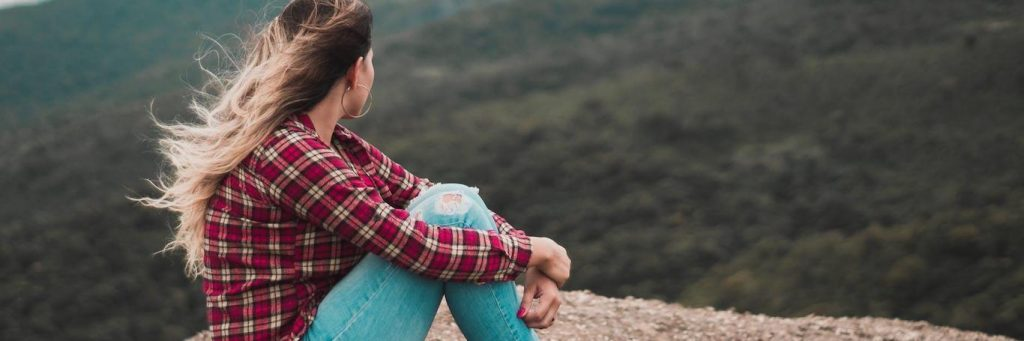 woman sits on rock in peaceful environment