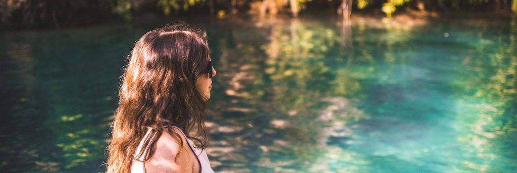 woman wearing sunglasses stands beside blue water lake thinking
