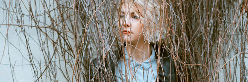 woman sadly stands between trees