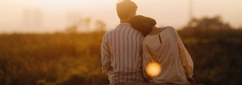 couple sits watching sunset while woman lying on partner shoulder