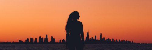 woman shadow facing backward standing in field red clear sky