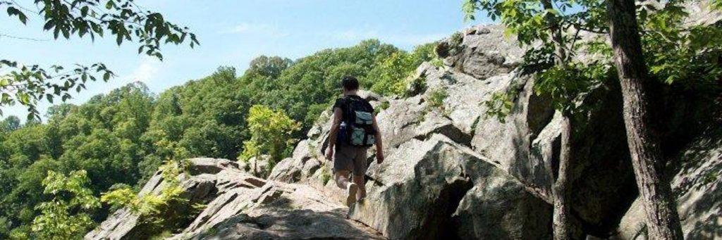 man wearing back bad climbs rock in beautiful blue clear sky