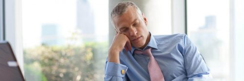 businessman sits hand on cheek tiredly sleeping in office