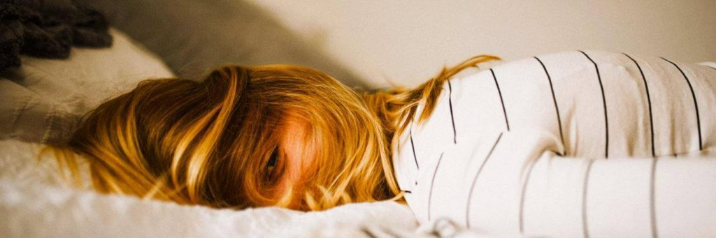 woman tiredly lies on bed having difficulty to sleep
