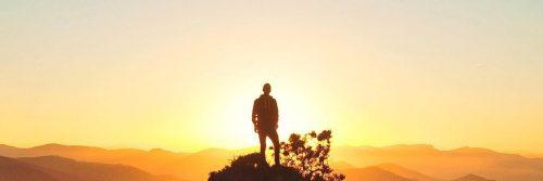 man stands on rock beautiful sunset scene