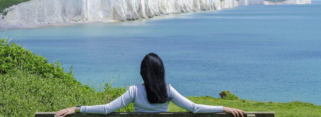 woman facing backward sits on bench looking at blue ocean