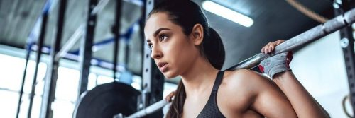woman carries barbell working out exercising in gym
