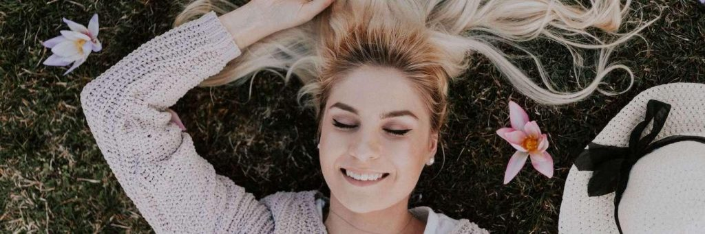 woman lies on grass eyes closed happily smiling gratitude life