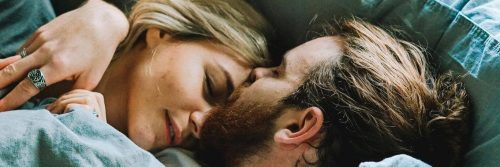 couple hugs lies on bed while man kissing on partner forehead