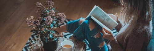 woman sits on floor beside side table tea cup reading book