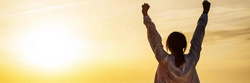 woman stands facing backward raising hands gratitude life in sunset sky