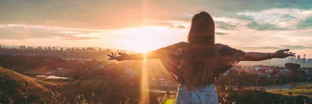 woman stands facing backward gratitude life in beautiful sunny sky