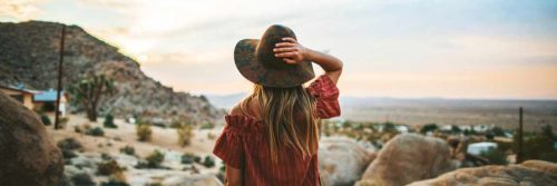 long blonde hair woman hand on hat stands on rock looking at desert mountain in blue cloudy sky