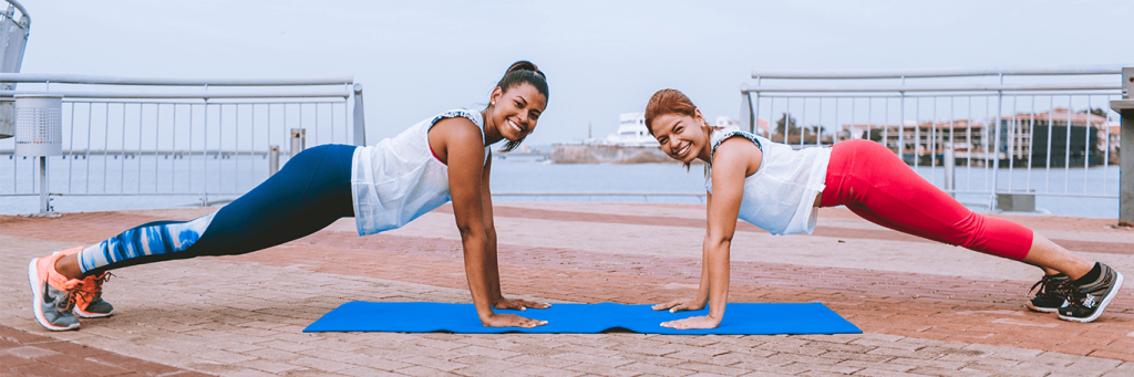 two women practice plank happily smiling on blue yoga mat near seaport