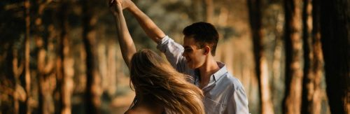 couple happily dances in forest in sunny sky