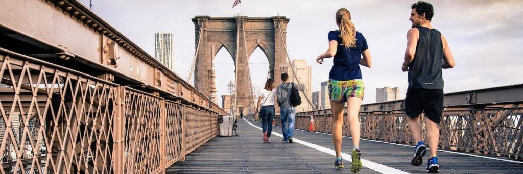 couple excitedly energetically exercises jogs along old bridge