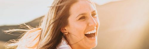 woman excited happy laughing in sunny sky