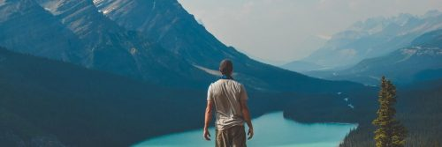 man stands beside lake looking at mountain in foggy weather