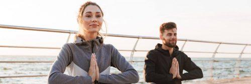 couple sits on bridge practices meditation