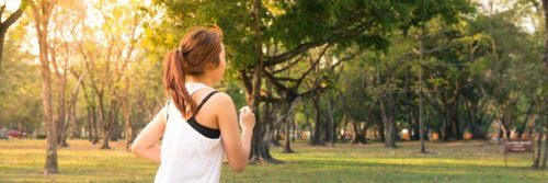 woman exercises jogs in park in beautiful sunny weather