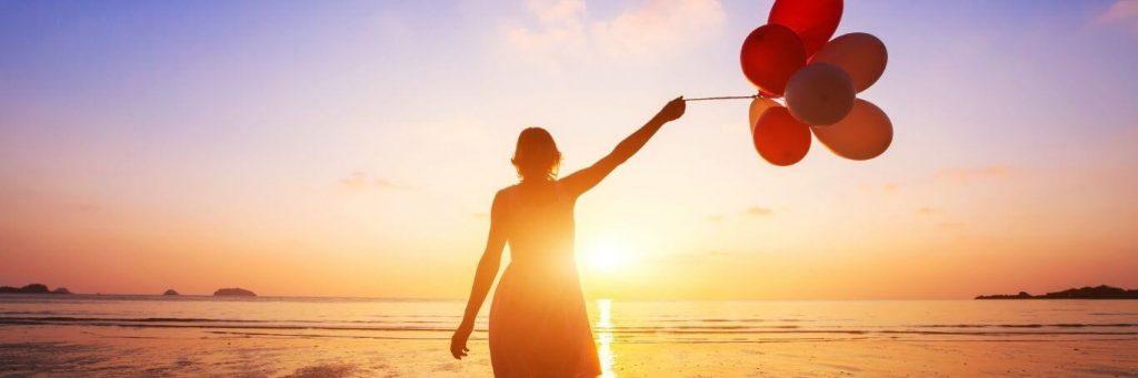 woman stands facing backward on beach holding balloons watching sunset