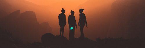 three women stand on rock in dark red sky