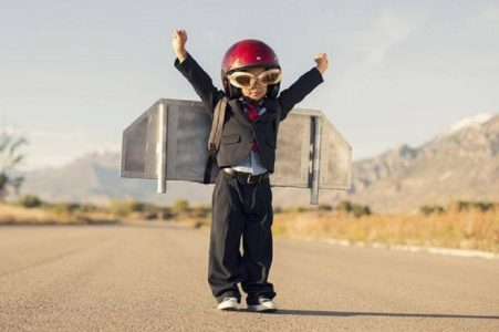 small kid stands alone raising hands carrying airplane designed bag